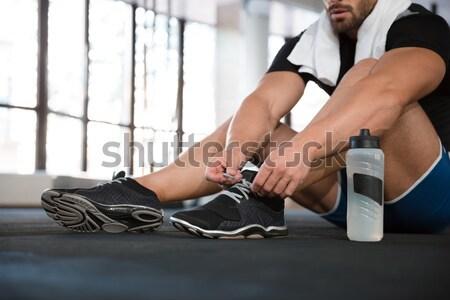 Sportsman ties his sneakers Stock photo © deandrobot