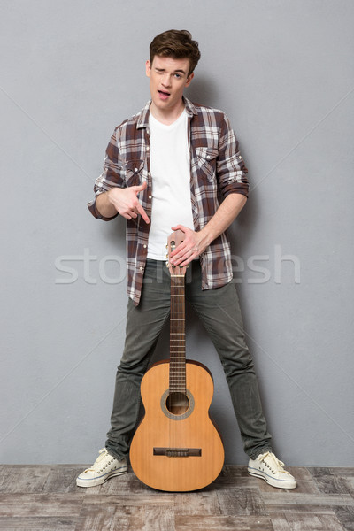 Young man winking and pointing finger on guitar  Stock photo © deandrobot