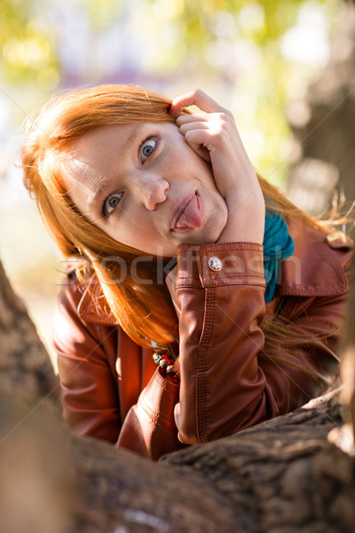 Pretty amusing redhead girl making funny face and showing tongue Stock photo © deandrobot