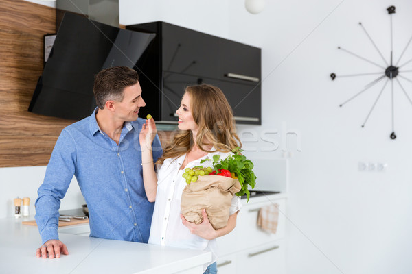 Happy couple with package of products flirting on kitchen  Stock photo © deandrobot