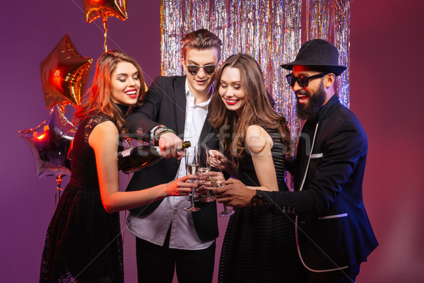 Group of happy young friends drinking champagne on party together Stock photo © deandrobot