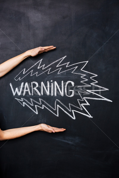Two hands showing warning drawn on blackboard Stock photo © deandrobot