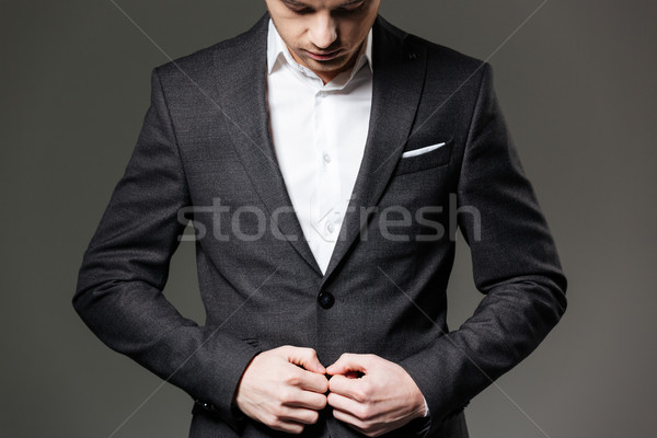 Handsome young businessman in black suit and white shirt  Stock photo © deandrobot