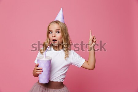 Happy amazed woman in party hat looking at camera Stock photo © deandrobot
