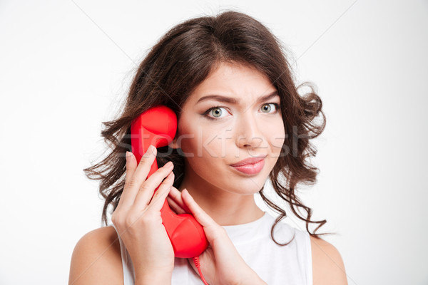 Woman covering microphone on phone tube Stock photo © deandrobot