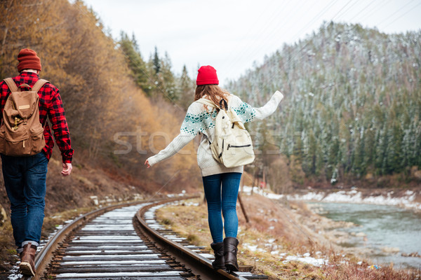 Beautiful young couple with backpacks walking along railroad Stock photo © deandrobot