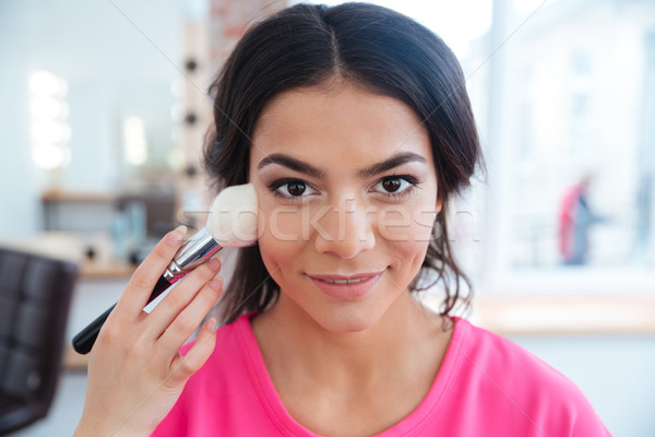 Female visagist with brush doing professional makeup to smiling woman Stock photo © deandrobot
