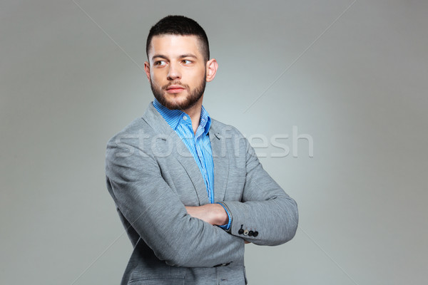 Businessman with arms folded looking away Stock photo © deandrobot