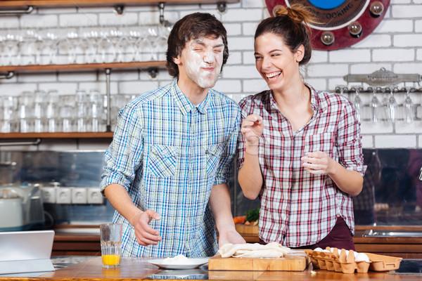 Funny couple kneading dough and having fun on kitchen Stock photo © deandrobot