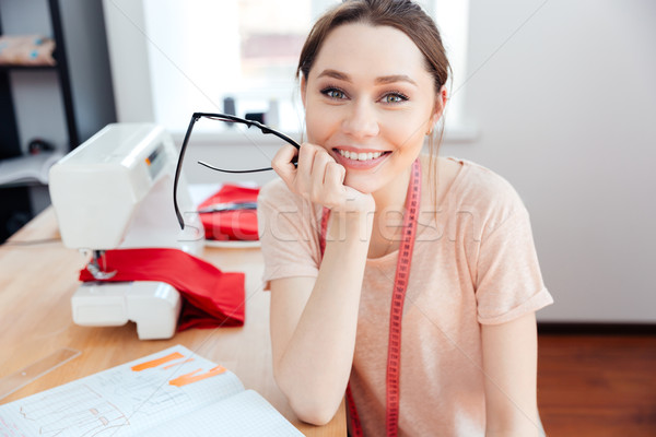 Cheerful woman seamstress sitting and smiling at work Stock photo © deandrobot