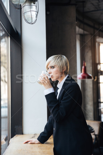 Pretty stylish blonde girl drinking at he windowsill in cafe Stock photo © deandrobot