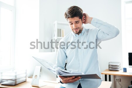 Businessman working with documents in folder Stock photo © deandrobot