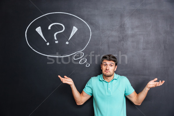 Confused perplexed young man shrugging shoulders over chalkboard background Stock photo © deandrobot