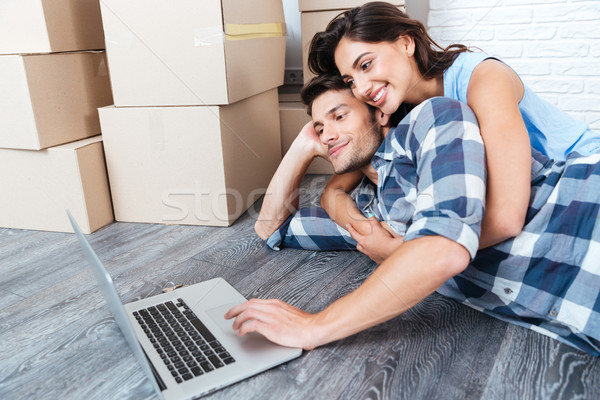 Couple using laptop computer in their new house Stock photo © deandrobot