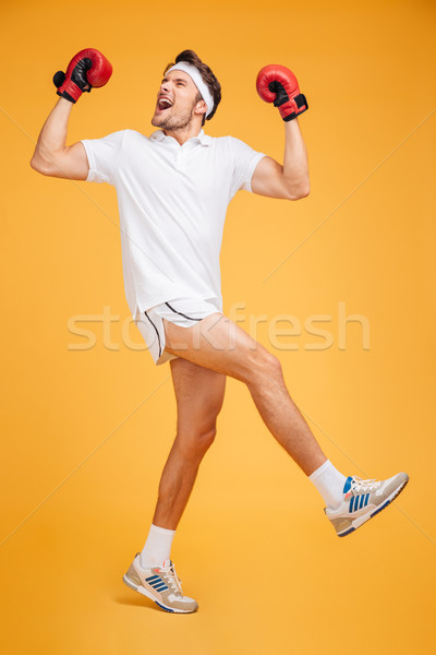 Joyful man boxer in red gloves dancing and celebrating success Stock photo © deandrobot