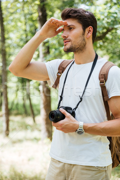 Man photographer holding camera and looking far away in forest Stock photo © deandrobot