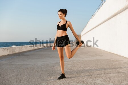 Beautiful attractive young woman exercising yoga on the beach Stock photo © deandrobot