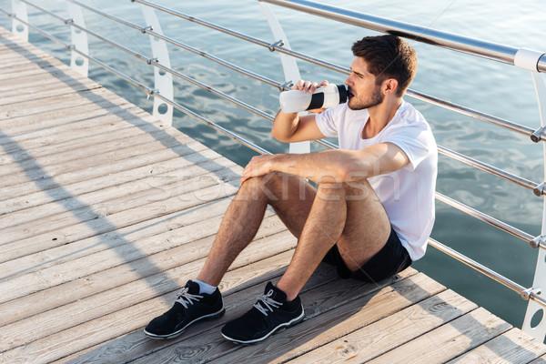 Mężczyzna sportowiec posiedzenia molo woda pitna atrakcyjny Zdjęcia stock © deandrobot
