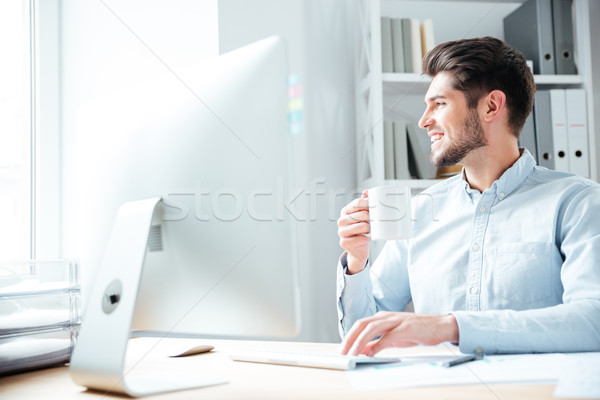 Young smiling businessman drinking coffee and looking away in office Stock photo © deandrobot