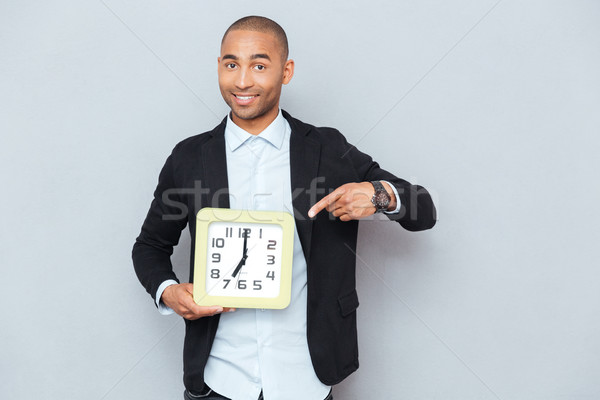 Happy african american man holding clock anf pointing on it Stock photo © deandrobot
