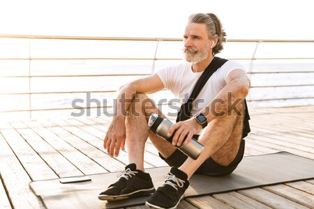 Serious man sitting at the beach shack Stock photo © deandrobot