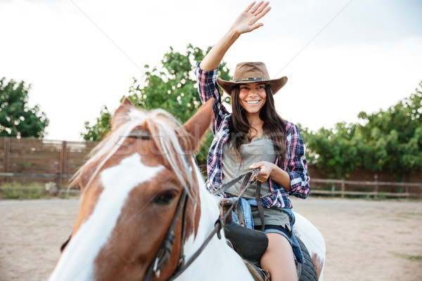 Smiling woman cowgirl riding a horse outdoors Stock photo © deandrobot