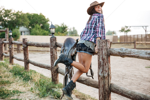 Cowgirl standing at the ranch fence Stock photo © deandrobot