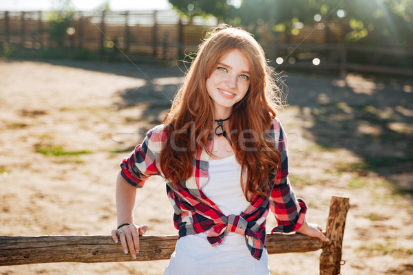 Portrait of pretty redhead cowgirl leaning on the ranch fence Stock photo © deandrobot