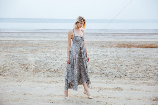 Woman in beautiful long dress walking tiptoes on the beach Stock photo © deandrobot