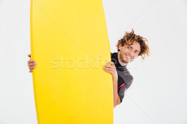 улыбаясь спортсмен глядя из доска для серфинга Сток-фото © deandrobot