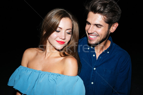 Happy young couple standing together at night Stock photo © deandrobot