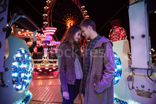 Tender young couple standing and hugging in amusement park Stock photo © deandrobot