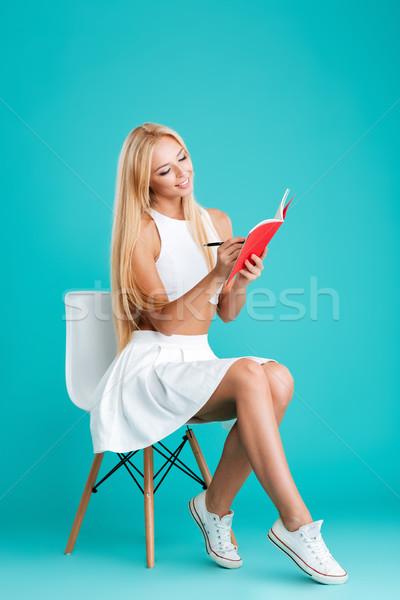 Foto stock: Sorridente · mulher · jovem · notas · sessão · cadeira