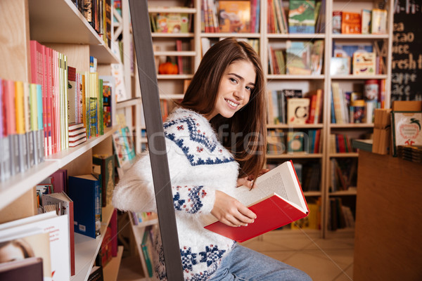 Smiling student reading a book at bookshelf in the library Stock photo © deandrobot