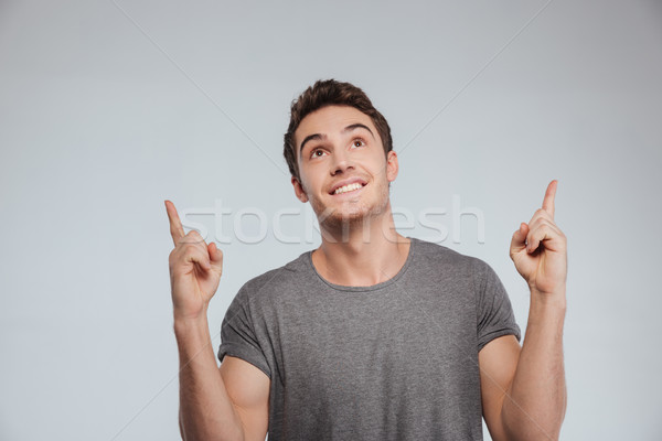 Portrait of a happy casual man pointing fingers up Stock photo © deandrobot