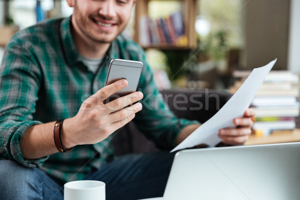 Cropped image of man with documents and phone Stock photo © deandrobot