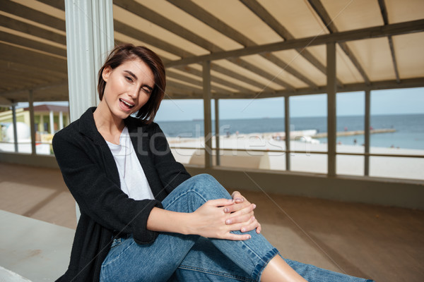 Cheerful woman sitting and winking in gazebo on the seaside Stock photo © deandrobot