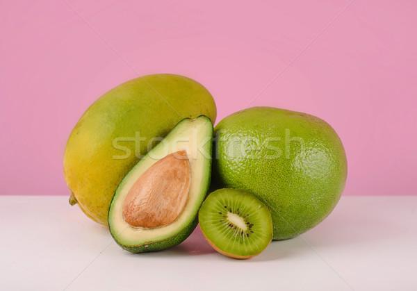 Green pomelo fruit, sliced avocado and kiwi on a table Stock photo © deandrobot