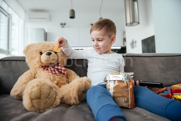 Küçük erkek oturma kanepe oyuncak ayı ev Stok fotoğraf © deandrobot