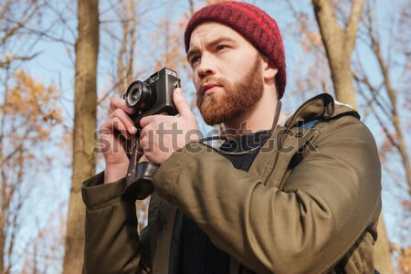 Bearded man using camera standing in the forest. Stock photo © deandrobot
