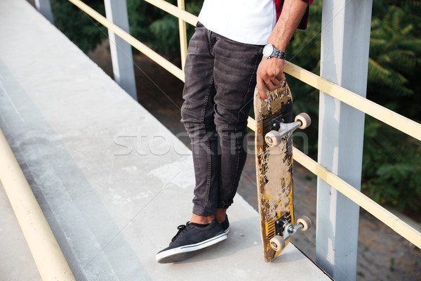 Cropped photo of young dark skinned man holding skateboard Stock photo © deandrobot