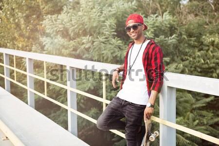 Cheerful dark skinned man holding skateboard Stock photo © deandrobot