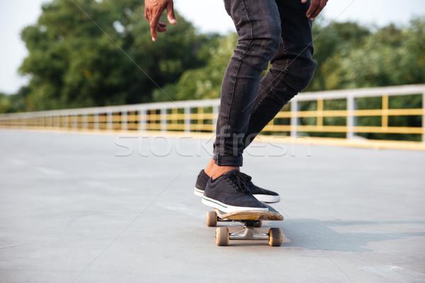Young dark skinned man skateboarding Stock photo © deandrobot
