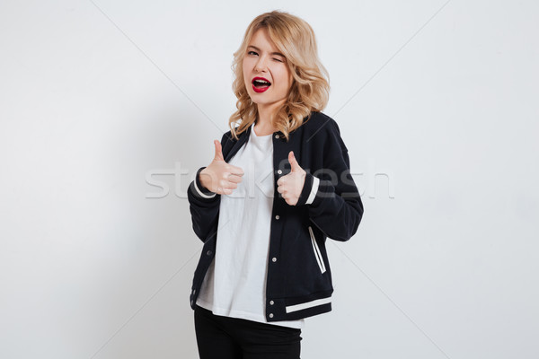 Playful pretty girl in casual clothes showing two thumbs up Stock photo © deandrobot