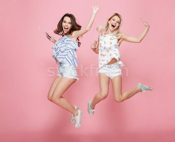 Due felice spensierato giovani donne jumping ascoltare musica Foto d'archivio © deandrobot