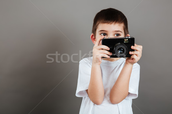 Handsome little boy standing and using photo camera Stock photo © deandrobot