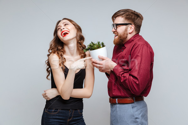 Stock photo: Male nerd presents the plant for girl