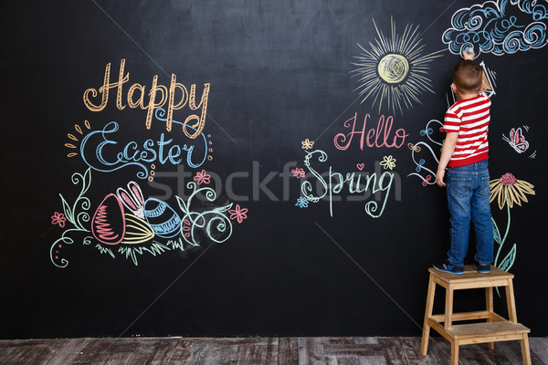 Little boy standing and drawing easter doodles Stock photo © deandrobot