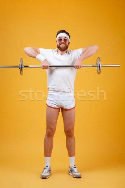 appy young sportsman make sport exercises with barbell Stock photo © deandrobot