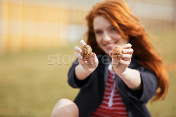 Girl with long ginger hair showing two painted easter eggs Stock photo © deandrobot
